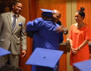 One HOPE graduate embraces Thomas Penny before crossing the stage to accept his certificate.