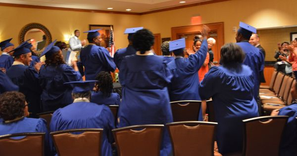 The Goodwill HOPE class of 2013 rises to their feet to applaud valadictorian Alex Holland.